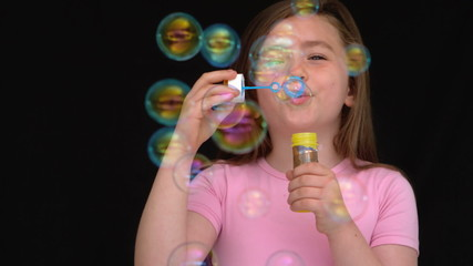 Happy girl playing with bubbles