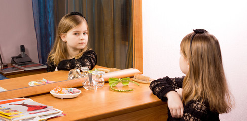 Little girl looking at herself in a mirror