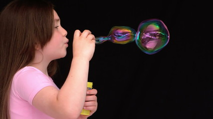 Little girl making bubbles