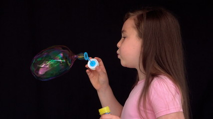 Cheerful girl making big bubbles