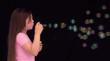 Side view of a little girl making bubbles