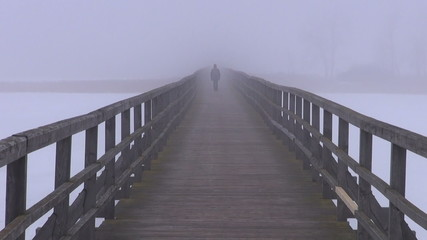 lonely  schoolboy walking in winter fog on wooden bridge