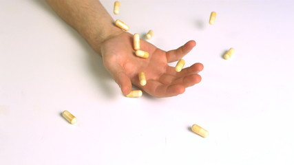 Hand falling with pills
