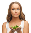 woman with spinach leaves on palms