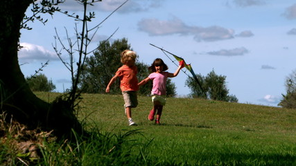 Two children running with kite