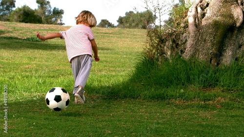 Child playing with football in slow motion