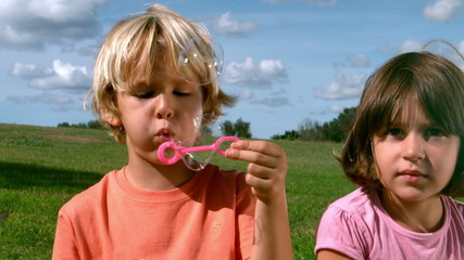 Small boy blowing bubbles with a girl
