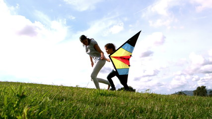 Woman and her daughter running with kite