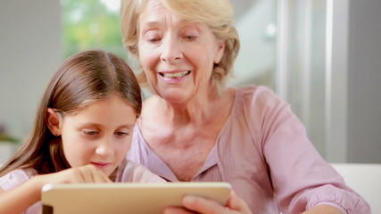 Child using tablet with her granny