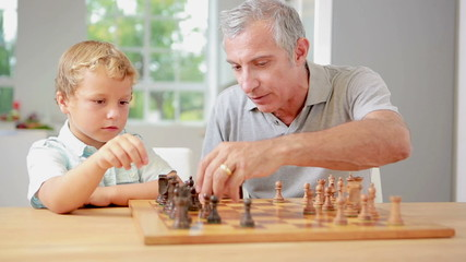 Child learning to play chess with his grandpa