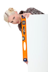 Woman with a spirit level and a board for message