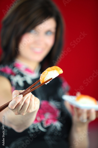 Woman eating sushi with chopsticks