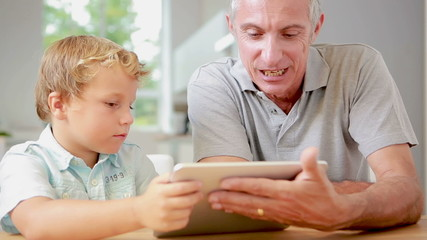 Child using tablet with his grandfather
