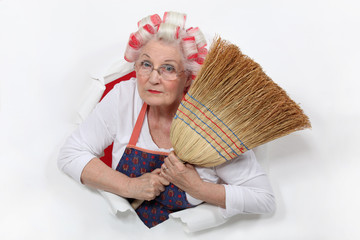 Granny with her hair in rollers holding a broom