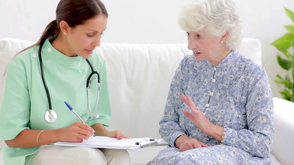 Elderly woman telling home nurse about back pain
