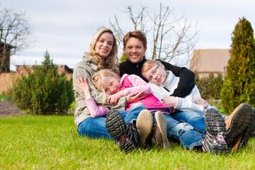 Eine Familie sitzt zusammen auf einer Wiese