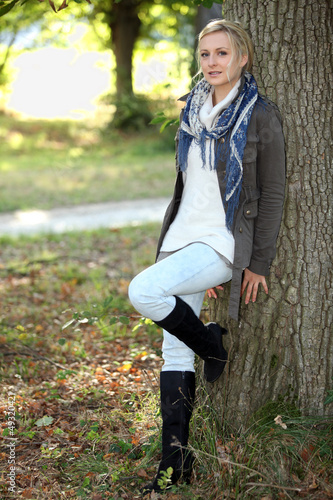 Woman leaning against tree