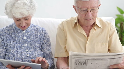 Old couple using a newspaper and a tablet