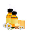bottles with essence oil, candles and chamomiles isolated on whi