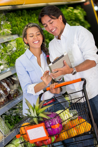 Couple with shopping list on a tablet
