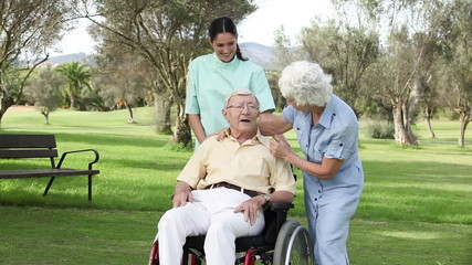 Woman and nurse talking to man in wheelchair