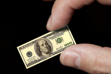 Fingers hold a small dollar note