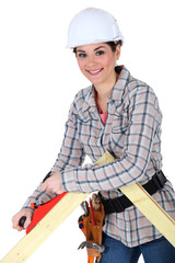 Female carpenter using a planer.