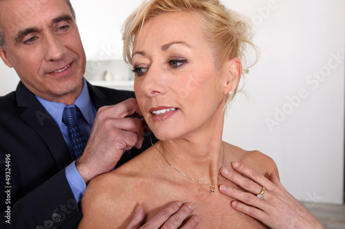 mature gentleman offering his lady a necklace