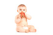 A 9 month old baby boy sitting and eating an apple