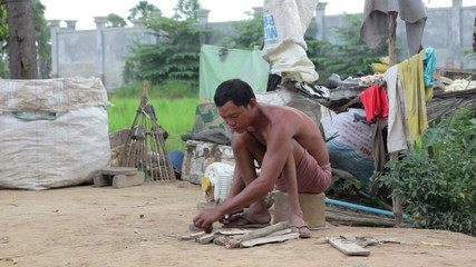 Father in slums preparing fire by cutting wood