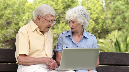 Old couple using a laptop