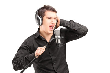 A male singer with headphones performing a song