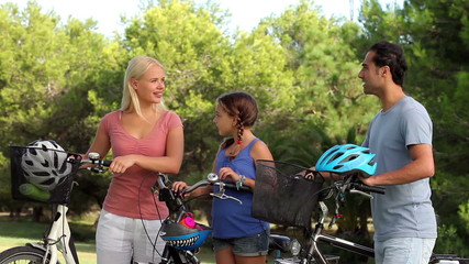 Discussing family with their bikes in park