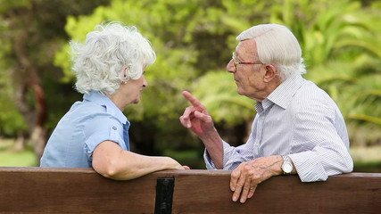 Old couple talking quietly on a bench