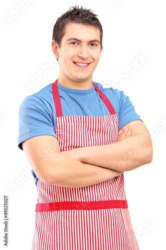A portrait of a young male wearing apron and posing