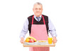 A smiling gentleman in apron carrying a tray with drinks and foo