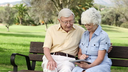 Old couple using a tablet on a bench