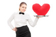 A waitress with bow tie holding a tray with red heart on it tray