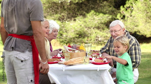 Father serving food to son at picnic table