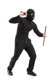 Full length portrait of a robber with mask holding a flashlight