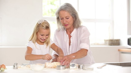 Little girl rolling out pastry with grandmother