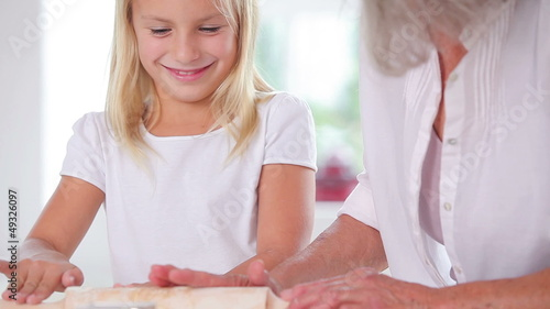 Granddaughter making biscuits with her grandmother