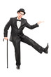 Young performer in black suit holding a cane and dancing