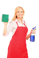 Mature female cleaner holding a liquid for spraying and a cloth