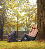 Young mother sitting in a park with her baby in a carrycot and t
