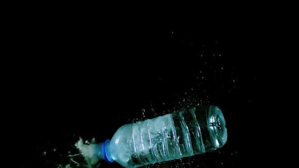 Bottle of water falling and spilling