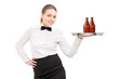 A waitress with bow tie holding a tray with two bottles of beer