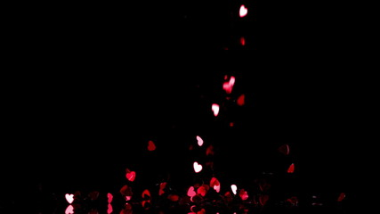 Heart confetti falling down on black background