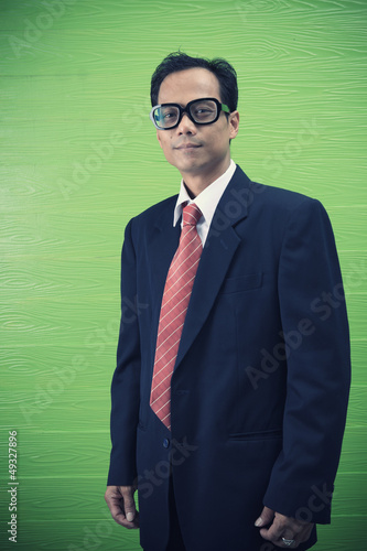 asian man in dark suit standing on green background