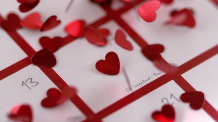 Red heart confetti dropping on calendar
